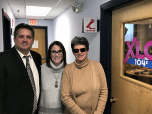 Three people pose outside the recording studio at XLO Radio. From left to right; Greg Donnelly, Vicki Greene and Jennifer Harnish.