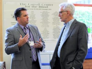 Gregory J. Donnelly (left), Carroll Center for the Blind President and CEO, talks with Thomas A. Croswell, Tufts Health Plan President and CEO in the lobby of the Rachel E. Rosenbaum Technology Center.