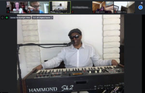 The legendary Ellis Hall smiles while seated behind a Hammond piano keyboard as he talks to students in the Introduction to Careers in Music program through Zoom.