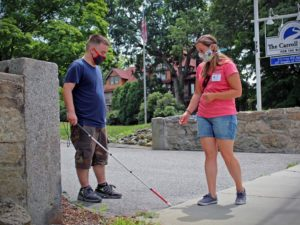 A student in the youth learning day program works on his Orientation & Mobility Skills with a Certified Orientation & Mobility Specialist at the foot of the Carroll Center's driveway.