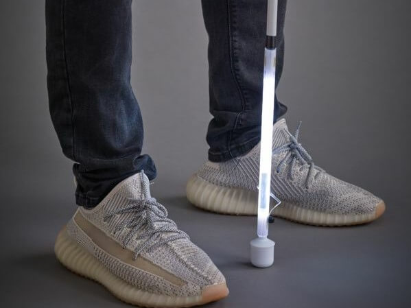 A man stands with an illuminated Gizahand LED Mobility Cane at his feet.