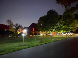 Nearly a dozen illuminated solar light posts line the Carroll Center for the Blind driveway at dusk.