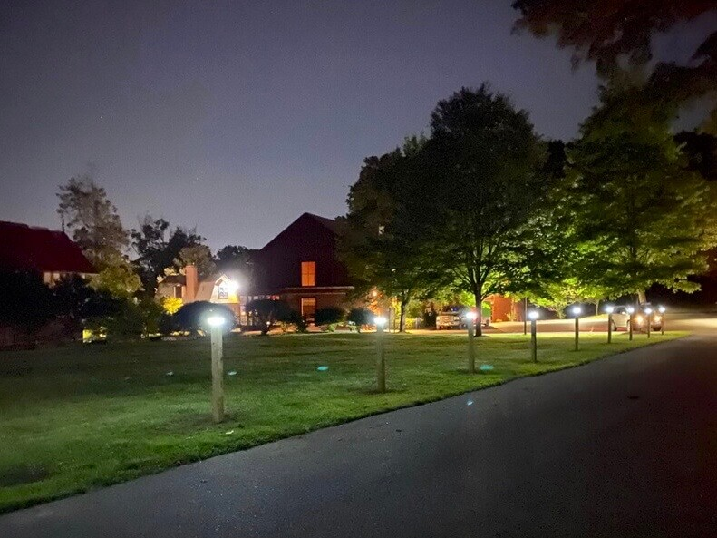 A completed Nearly a dozen illuminated solar light posts line the Carroll Center for the Blind driveway at dusk.
