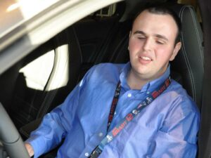 Adam Roberge, wearing a blue button down shirt with a Patriots lanyard around his neck, smiles as he sits in the driver's seat of a Mercedes-Benz on his first day of work at the dealership.