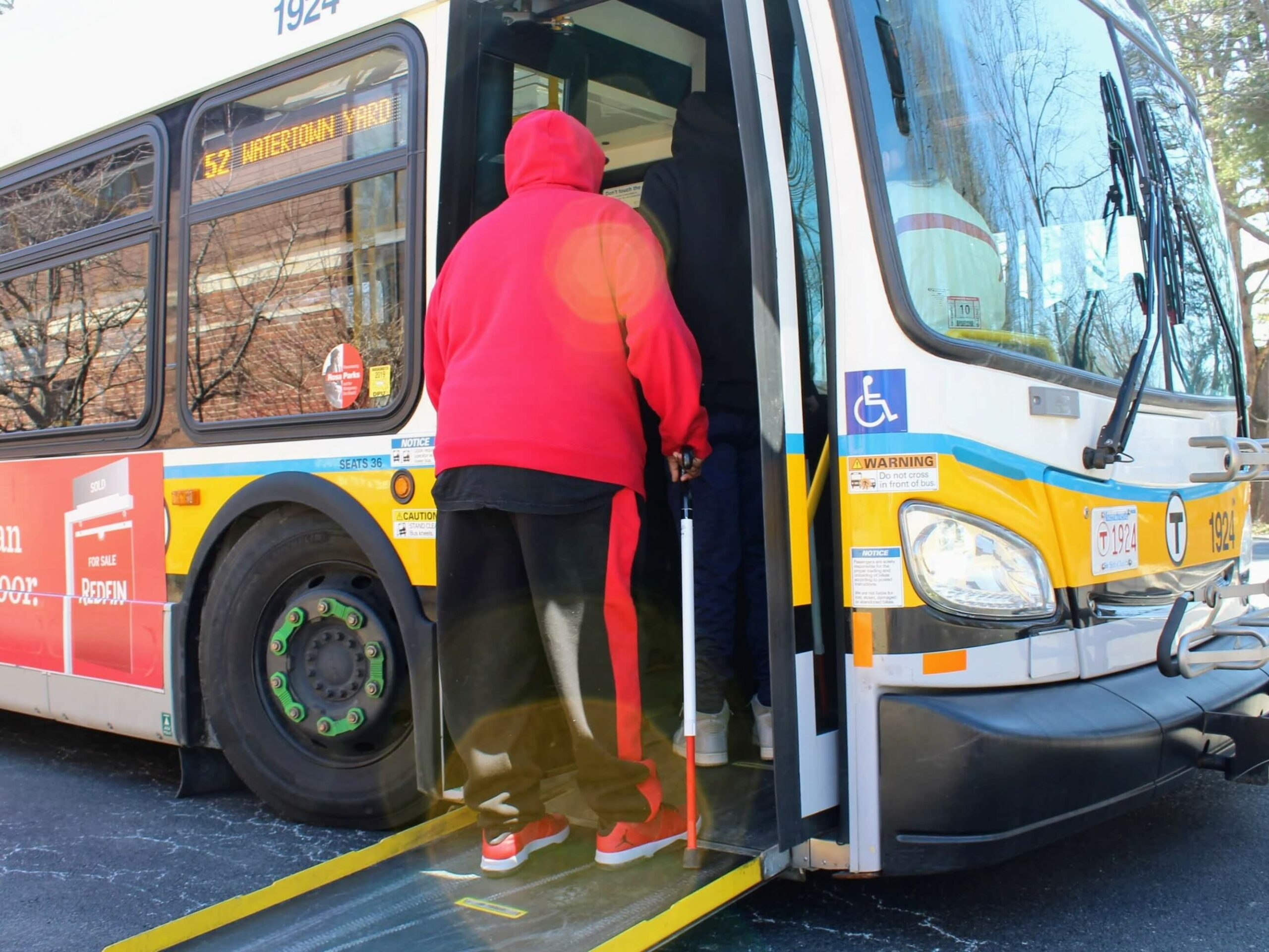 During an MBTA Travel Training accessibility session held in the Carroll Center for the Blind's parking lot, a client steps onto a new 52 bus.