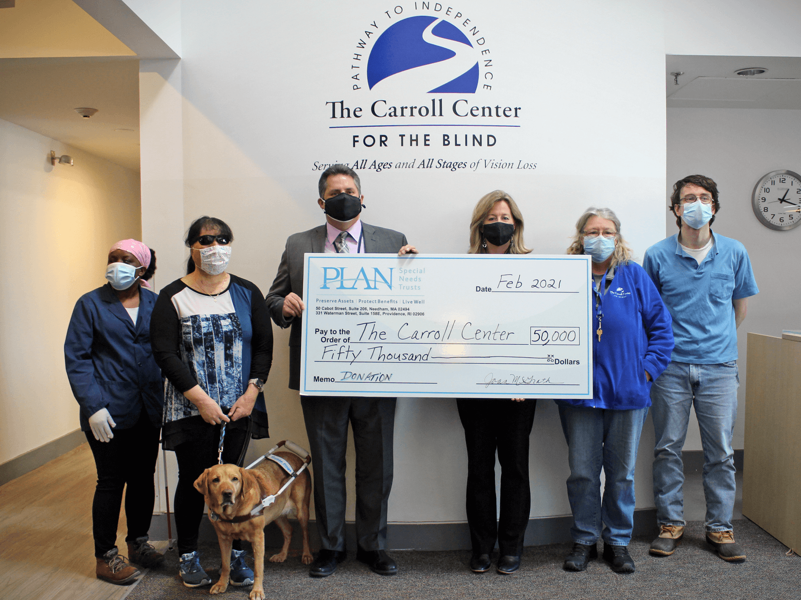 In the lobby of the Carroll Center for the Blind, Joan McGrath, executive director of PLAN of MA & RI presents Greg Donnelly, President & CEO of the Carroll Center for the Blind with a giant cardboard check.