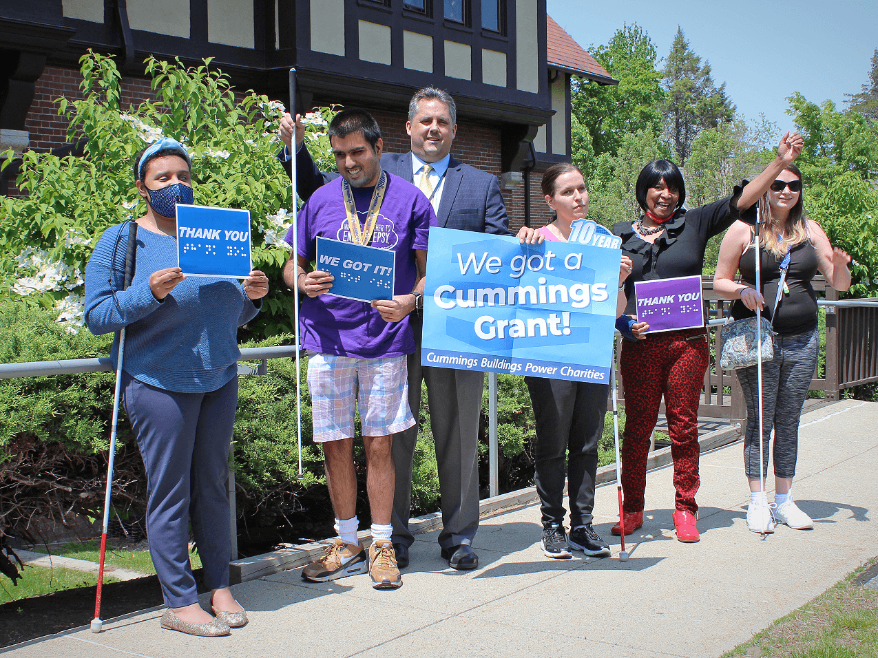 """Gregory J. Donnelly, President and CEO of the Carroll Center for the Blind, celebrates the Cummings Foundation Grant by holding up signs with five Carroll Center clients outdoors. The signs read, """"We Got a Cummings Grant!"""""""