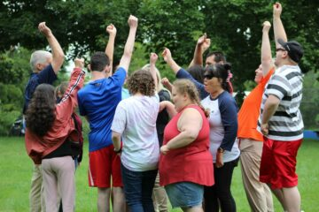 A group of over a dozen students huddle together and raise their fists in the air at the conclusion of an activity on the lawn.