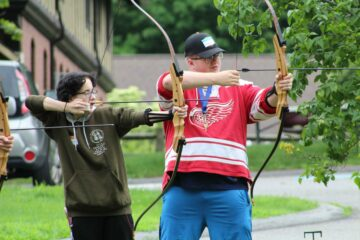 Two youth in transition students pull back their bows during archery.