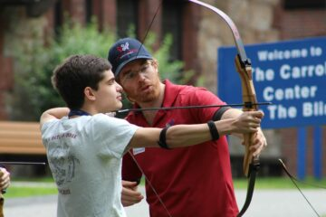 An instructor works with a youth in transition student during archery.