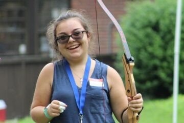 A teenager in the youth in transition program smiles widely after firing an arrow during archery.