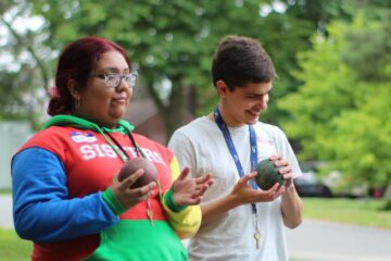 On field day, two youth in transition students laugh as they play Bocce.