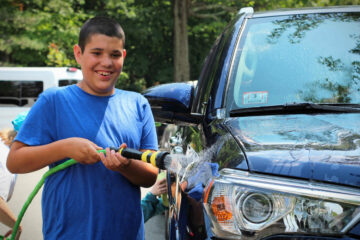 A smiling Carroll Teen student hoses off a large blue Toyota Four Runner.