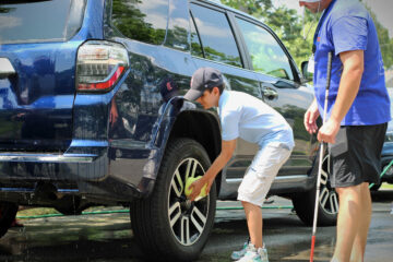 A Carroll Teen summer student bends down to wash the wheels of a blue Toyota four runner with a yellow sponge.