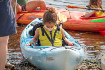 A Carroll Kids student gets situated in the front seat of a two person kayak.