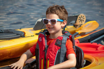 While floating back to the dock, a student in the Carroll Kids program smiles from his kayak.