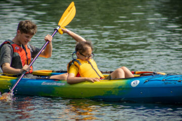 A Carroll Kids student sitting in the front of a two person kayak splashes his kayak buddy with a sponge.