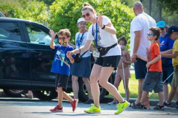 An instructor and Carroll Kids student hold hands and wave at the camera as they walk across a parking lot.