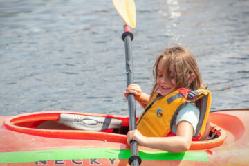 As she floats in her kayak, a Carroll Kids student smiles widely as she paddles.