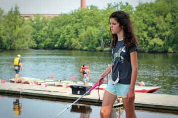 A summer program student walks up the dock at Community Rowing in Brighton.