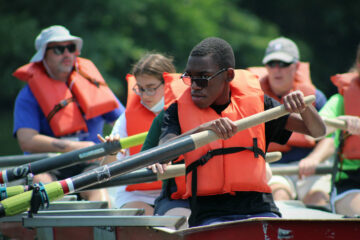 On a boat, several summer program students row in unison.