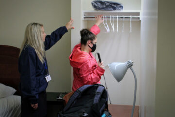 A youth in transition program student explores a closet as an instructor helps get her oriented to her room.