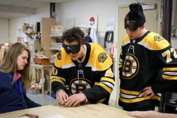 In the Carroll Center's manual arts shop, Tuukka Rask and Frank Vatrano of the Boston Bruins explore a tactile map while occluded.
