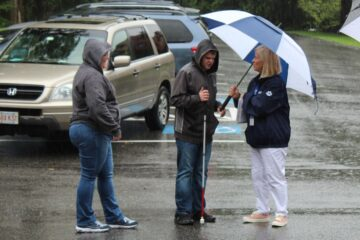 While standing beside their car in the rain, a mother and son talk with a Carroll Center staff member as they move in.