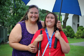During move-in day at the Carroll Center for the Blind, a smiling mother and daughter pose under an umbrella as they say goodbye to each other.