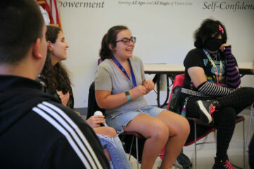 During icebreakers, a group of youth in transition summer program students sit around a circle in the technology center auditorium at the Carroll Center for the Blind.