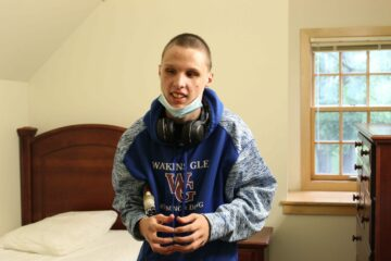 A student poses for a photo in his room after arriving to campus on move-in day.