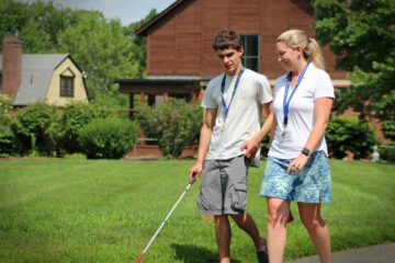 A Youth in transition student walks along the driveway at the carroll center during an orientation and mobility lesson.