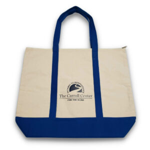 Carroll Center for the Blind Tote Bag features beige canvas material on the body of the tote. The handles and bottom of the tote bag are blue. A small, black Carroll Center for the Blind logo appears on the middle of the tote.