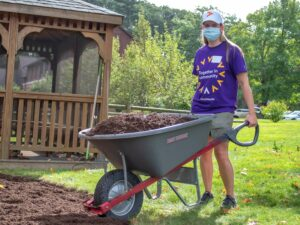 A volunteer from Point 32 Health wearing a purple company shirt empties a wheelbarrow filled with dirt in front of a gazebo at the Carroll Center for the Blind.