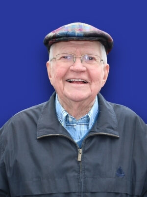 John Jack McCarthy smiling. He is an older white male wearing a plaid flat cap, glasses and a black quarter zip.