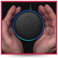 A person cups their hands around an Amazon Echo device.